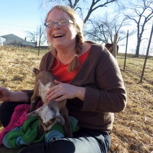 Woman sitting on the ground wearing glasses, smiling and holding a baby goat in the sunshine outside.