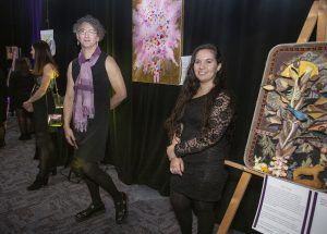 Two white women stand in front of an art installation. They are both wearing black dresses. The one on the left has short, curly, grey hair and is wearing glasses and a purple scarf. The one on the right has long dark hair and is smiling into the camera.