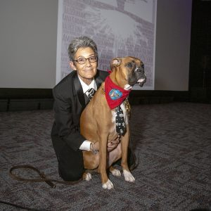 A woman wearing a suit kneels down next to a brown dog with a black face. The dog is wearing a red bandana and is on leash. The woman has short grey hair and is wearing glasses and smiles into the camera.